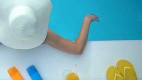 Женщина в большой белой шляпе играя с водой в бассейне, каникулах в гостинице сток-видео