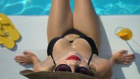 Женщина в большой шляпе играя с водой в бассейне и смотря камеру, взгляд сверху акции видеоматериалы
