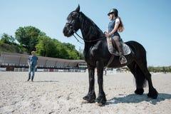 Женщина в верховой лошади шлема и смотреть человека стоя позади Стоковое Изображение