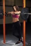 Женщина в весах спортзала поднимаясь на штанге Стоковая Фотография RF
