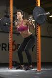 Женщина в весах спортзала поднимаясь на штанге Стоковые Изображения RF