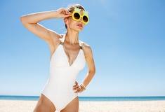 Женщина в в стиле фанк стеклах ананаса смотря в расстояние на пляже Стоковая Фотография RF