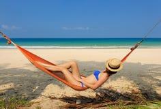 Женщина в гамаке на пляже стоковые фото