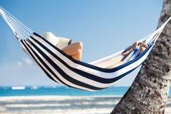 Женщина в гамаке на пляже Стоковое фото RF