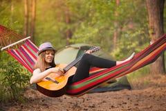 Женщина в гитаре игры шляпы и ослаблять в гамаке вися среди сосен в предпосылке стоковое изображение rf
