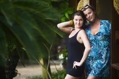 Женщина в голубом платье вместе с молодой красивой женщиной в черном платье стоит на двери ее hous стоковая фотография rf
