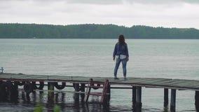Женщина в голубых прогулках одежд на старых деревянных взглядах пристани на камере после этого поворачивает вокруг и показывает в акции видеоматериалы