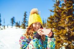 Женщина в горах для того чтобы сфотографировать на телефоне стоковые изображения