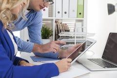 Женщина в голубом блейзере и человек работают в офисе и смотрят a Стоковые Изображения
