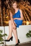 Женщина в голубом платье сидя Outdoors на ноче Стоковые Изображения