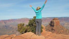 Женщина в гранд-каньоне приходит к месту наблюдения и оружиям вверх