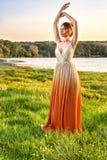 Женщина в длинном блестящем платье на заходе солнца Платье градиента девушки симпатичное красивейший взгляд ландшафта Моды лета г стоковая фотография rf
