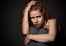 Женщина в депрессии и отчаянии плача на черной темноте стоковое изображение