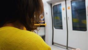 Женщина в желтой блузке получая домашний поезд, образ жизни приедаемости, общественный транспорт сток-видео