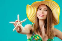 Женщина в желтой шляпе держа белую раковину Стоковое Изображение