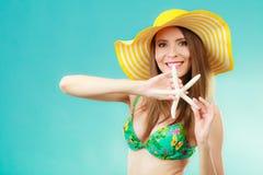 Женщина в желтой шляпе держа белую раковину стоковые изображения rf