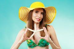 Женщина в желтой шляпе держа белую раковину стоковая фотография rf