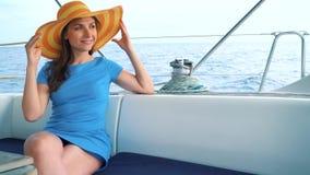 Женщина в желтой шляпе и голубой девушке платья отдыхает на борту яхты на сезоне лета на океане сток-видео