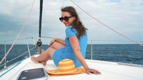Женщина в желтой шляпе и голубом платье отдыхает на борту яхты на сезоне лета на океане видеоматериал