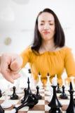 Женщина в желтом платье сидя перед шахматами - ответная часть проверки стоковые изображения