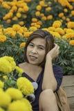 Женщина в желтом саде цветков ноготк или erecta Tagetes в саде стоковое фото