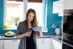 Женщина в женщине кухни лить стекло воды стоковое изображение rf