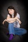 Женщина в джинсах сидя на поле Стоковая Фотография
