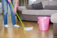 Женщина в защитных перчатках используя влажн-mop пока очищающ пол стоковые фото