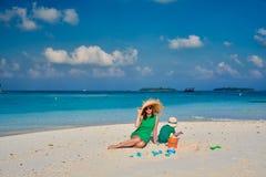 Женщина в зеленом платье с годовалым мальчиком 3 на пляже стоковое изображение rf