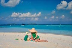 Женщина в зеленом платье с годовалым мальчиком 3 на пляже стоковые фотографии rf