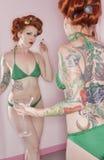 Женщина в зеленом бикини смотря себя в зеркале стоковые фото