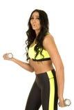 Женщина в зеленом и черном фитнесе одевает бортовые весы Стоковые Изображения