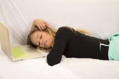 Женщина в зеленом layign юбки с спать компьтер-книжки стоковая фотография