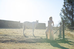 Женщина в золотом платье рядом с белой лошадью Стоковые Фото