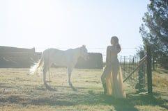 Женщина в золотом платье рядом с белой лошадью Стоковая Фотография