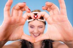 Женщина в изумлённых взглядах лыжи делая пальцы символа сердца Стоковое фото RF
