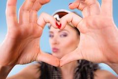 Женщина в изумлённых взглядах лыжи делая пальцы символа сердца Стоковая Фотография RF