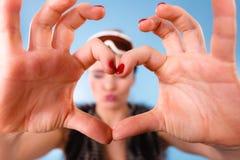 Женщина в изумлённых взглядах лыжи делая пальцы символа сердца Стоковое Изображение