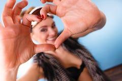 Женщина в изумлённых взглядах лыжи делая пальцы символа сердца Стоковое Фото