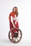Женщина в длинной красной юбке стоя близко колесо  стоковая фотография rf