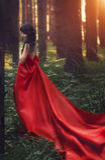 Женщина в длинном красном платье самостоятельно в лесе фантастичном и myst Стоковая Фотография RF