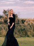 Женщина в длинном черном платье Стоковое Фото