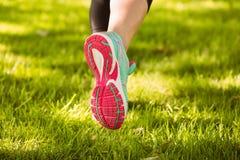 Женщина в идущих ботинках бежать на траве Стоковое Изображение