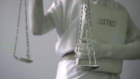 Женщина в каменном костюме статуи Femida богиня правосудия на белой предпосылке в одной руке держа масштабы видеоматериал