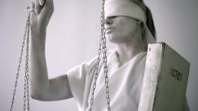 Женщина в каменном костюме статуи Femida богиня правосудия на белой предпосылке в одной руке держа масштабы акции видеоматериалы