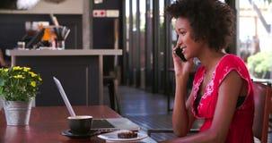 Женщина в кафе работая на компьтер-книжке и отвечая телефоне сток-видео