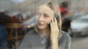 Женщина в кафе работая на компьтер-книжке и отвечая телефоне акции видеоматериалы