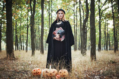 Женщина в костюме ведьмы хеллоуина в лесе Стоковое Изображение