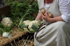 Женщина в костюме пока собирающ луки от тележки вполне veg Стоковое Изображение RF