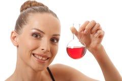 Женщина в костюме спорт держит склянку с красной жидкостью стоковое изображение rf